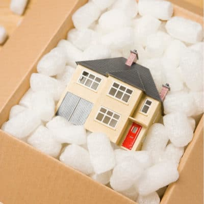 Photo of a model house in a cardboard box full of packing material representing moving back in with parents