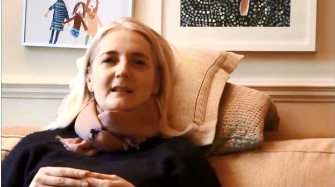 Catherine Hale, a woman with shoulder length blonde hair, shown top half resting against some pillows