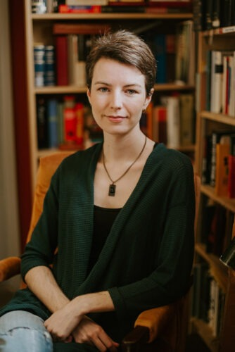 Photo of Allison Alexander by Carrie Lynn Unger Photo. A pale-skinned woman with short dark hair sits in front of a bookshelf, looking at the camera with a slight smile